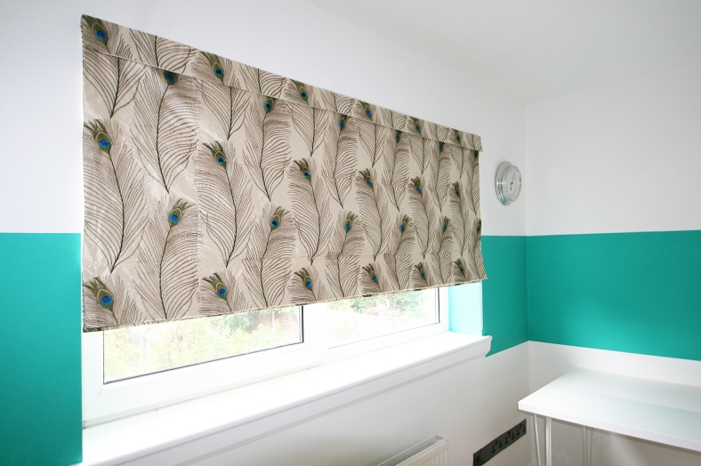 Painted wide horizontal green stripe on white wall with peacock fabric blind