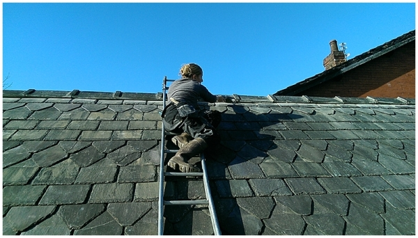 Lady builder pointing up ridge tiles on traditional roof