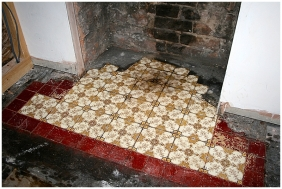 Original yellow and black Edwardian hearth tiles in fireplace