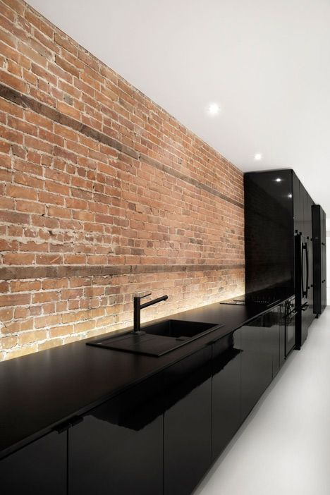 Bare brick wall in minimalist black kitchen