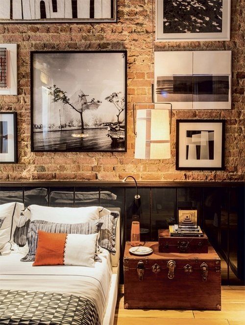 Bare brick enlivened by cool black framed pictures