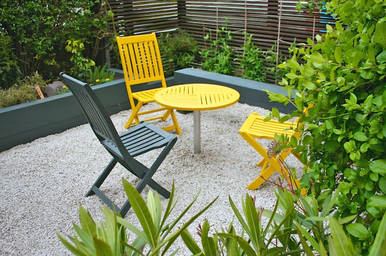 Grey and yellow painted furniture in grey and white garden